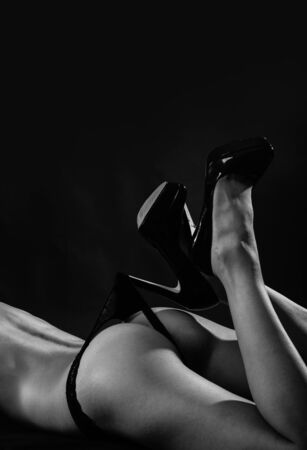 Seduction tactics. Sexy buttocks. Perfect female buttocks. Fit buttocks and legs wearing high heel shoes. Undressing black lace panties from buttocks