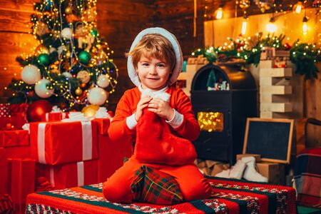 Christmas stocking. Open-ended Games. A little boy in warm clothes sitting and playing with textile toys. Christmas miracle and new year feelings. First memory of childhood.