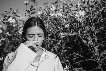 The girl suffers from pollen allergy during flowering and uses napkins. Young woman got nose allergy, flu sneezing nose. Woman is blowing her nose near flowers in bloom. Allergy. Stock Photo