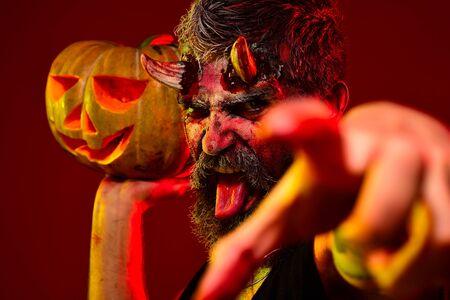 Devil man with bloody eyes hold pumpkins. Happy Halloween. Devil vampire man. Halloween Scene with bloody man devil. Devil in wicked witch hat. Demon for Halloween party. Halloween demon.