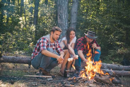 Company having hike picnic nature background. Friends roasting hotdogs on sticks at bonfire and having fun at camp fire. Company friends spend great time picnic or barbecue near bonfire.