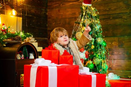 Cheerful cute child opening a Christmas present. Happy child with Christmas gift box. Winter kid. Funny kid holding Christmas gift. Cute little child is decorating the Christmas tree indoors.
