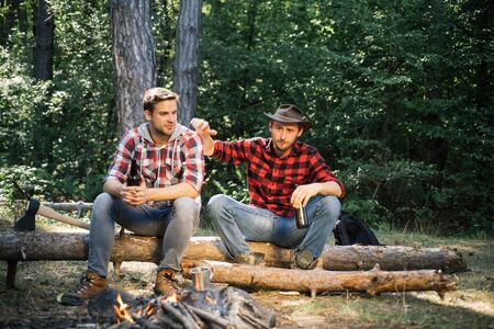 Young people enjoying picnic in park on summer day and drinking beer. Tourism concept. Picnic friends. Two friends lumberjack worker sitting in the forest and drinking beer.