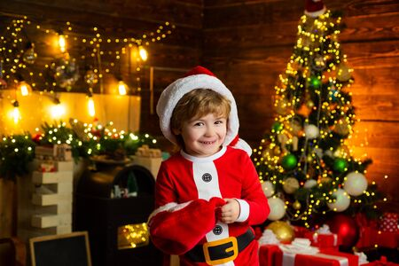 Buy christmas gifts online. Christmas shopping concept. Holidays and winter childhood concept. Smiling little boy in Santa helper hat over christmas tree at home background. Stock Photo