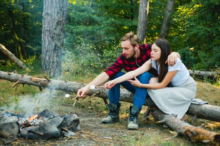 Summer lifestyle. Couple in love having hike picnic nature background. Funny couple eating roasted marshmallows while camping near the lake. Couple in love enjoying picnic in the forest. Reklamní fotografie