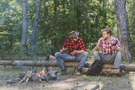 Company adult friends relaxing near campfire. Group of two male backpackers relaxing near campfire. Two friends lumberjack worker sitting in the forest and drinking beer. Reklamní fotografie