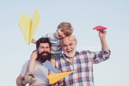 Happy fathers day. Childhood concept. Happy grandfather father and grandson with toy paper airplane over blue sky and clouds background.