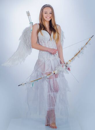 Cupid girl aiming at someone with an arrow of love. Girl dressed as an angel on a light background. Love concept. Angel children girl with white wings. Banco de Imagens