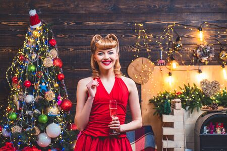 Beautiful blonde woman in red Christmas dress is standing in room with decoration near shiny Christmas tree and fireplace with garlands lanterns.