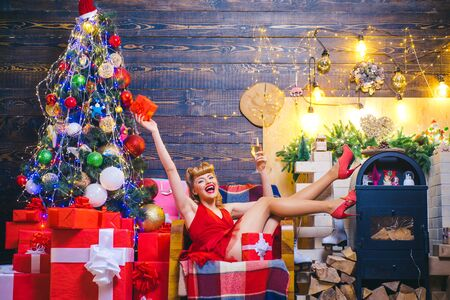 Happy woman with Christmas gift over Christmas interior background. Beauty Christmas fashion model girl holding xmas gift box. Stok Fotoğraf