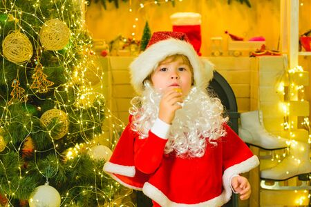 Merry Christmas. Santa - funny child picking cookie. Santa Claus takes a cookie on Christmas Eve as a thank you gift for leaving presents. Greeting Christmas card. Stock Photo