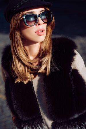 Beautiful woman in fur, urban style accessories and sunglasses. Lynx fur fashion beauty. Model looking at camera wearing stylish clothes and accessories. Luxury lifestyle and fashion concept.
