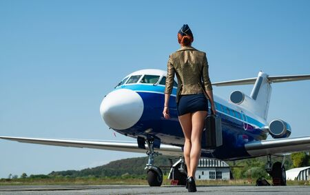Stewardess in blue uniform - back view. Pretty female flight attendant in airport. Charming stewardess dressed in blue uniform. Traveling and jet plane flying. Traveling and jet plane flying concept