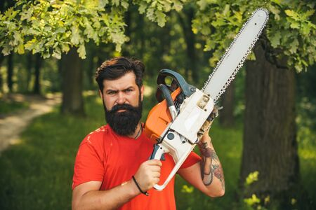 Lumberjack on serious face carries chainsaw. Deforestation is a major cause of land degradation and destabilization of natural ecosystems. Man doing mans job.