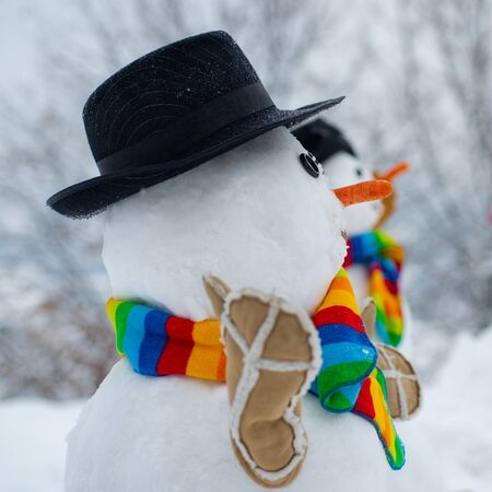 Happy snowman standing in winter Christmas landscape. The snowman is wearing a fur hat and scarf. Merry Christmas and Happy new year