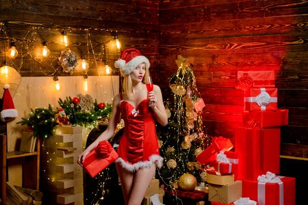 Beautiful young woman in Santa Claus clothes over christmas decorated interior background. Christmas interior. Present box. Xmas tree. Sexy hot blonde Snow Maiden.
