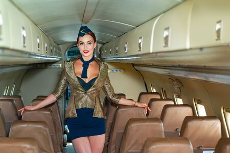 Flight attendant uniform. Female flight attendant. Airline. Beautiful charming stewardess dressed in official blue uniform staying inside the plane in airport. Plane travel.