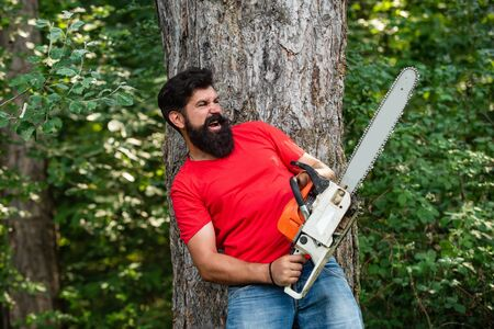 Lumberjack with chainsaw on forest background. Man doing mans job. Lumberjack with chainsaw in his hands. Lumberjack concept. Firewood as a renewable energy source. Stock Photo