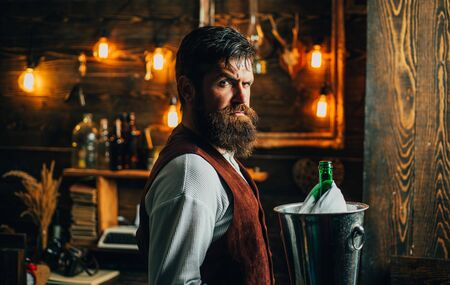 Handsome bearded barman with long beard and mustache has stylish hair on serious face. Man in vintage waistcoat. Brutal waiter. Vintage interior. Swag waiter with beard holds bucket with champagne in ice.