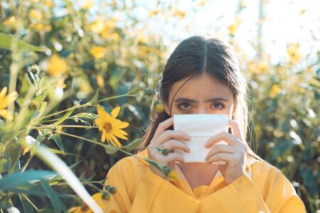 Flower allergy. Charming girl is blowing her nose near autumn yellow flowers in bloom. Closeup portrait of sneezing girl. Attractive woman outdoor with tissue having allergy. Stock Photo