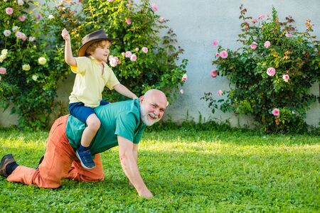 Senior man with grandson jogging in park. Cute child boy hugging his grandfather. Child with Grandfather dreams in summer in nature. Grandfather with son in park. Men generation. Stok Fotoğraf