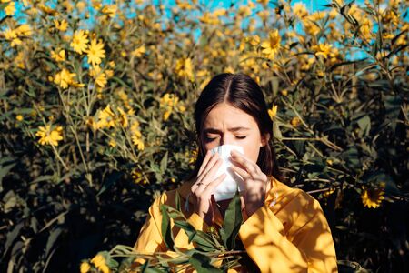Pollen allergy concept. Young woman is going to sneeze. Closeup portrait of sneezing girl at yellow flowers background. Beautiful girl having an allergic reaction to flowers.