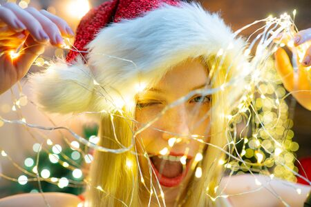 Sexy Santa woman in christmas lights wink and flirt at camera. Happy winter holiday. Merry Christmas and Happy New Year. Christmas eve. Snow Maiden beautiful young girl.