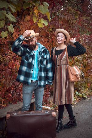 Smiling happy girl and bearded man in hat with large vintage looking bag. Guy wearing plaid shirt and femme in hipster autumnal dress. Stylish lovers. Fall hipster outfit concept. Stock Photo