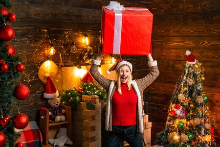 Christmas feellings. Blonde in christmas hat and gifts celebrating christmas holidays having big box.