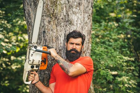 Lumberjack worker standing in the forest with chainsaw. Deforestation is a major cause of land degradation and destabilization of natural ecosystems.