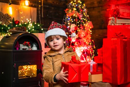Childhood memories. Present box. Santa little helper. Little Santa Claus helper elf with a magic gift for Christmas. Cute little santa baby with New years gifts on Christmassy background. Archivio Fotografico - 132738715