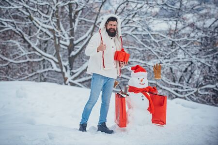 Handsome Winter Man with gift and snowman in frosty winter Park. Fashion man with Christmas present box. Handsome Santa Claus.
