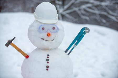 Snowman worker on snow background. Funny snowman in work helmet on snowy field. Handmade snowman in the snow outdoor.