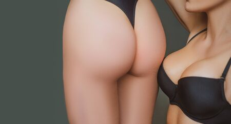 Two young sexy attractive women showing their good forms. Close up photo of sexy fit ass and big natural boobs in black classic lingerie. No plastic surgery concept Reklamní fotografie