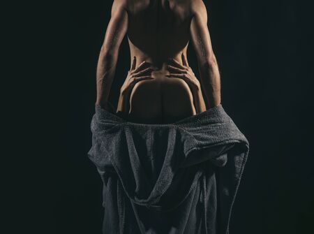 Muscular handsome man geting charge out of his sexy woman. Girl holding mans waist. Sexy couple in love. Play of light and shade. Couple foreplay and blowjob concept.