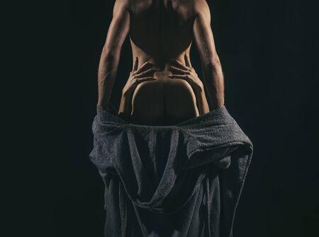 Uomo bello muscoloso che si carica della sua donna. La holding della ragazza equipaggia la vita. Coppia sexy innamorata. Giochi di luci e ombre. Concetto di coppia e pompino. Archivio Fotografico