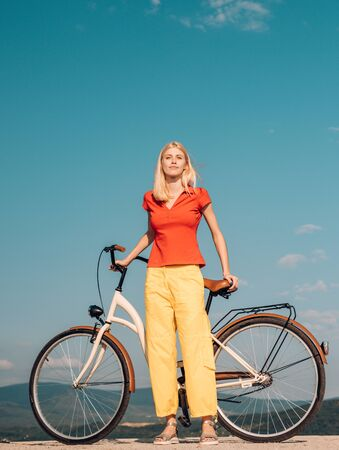 Pretty blonde woman enjoy her walk with bike. Cycling concept. Beautiful woman took a break while riding her vintage bicycle at good sunny day. Summer holidays and carefree time.