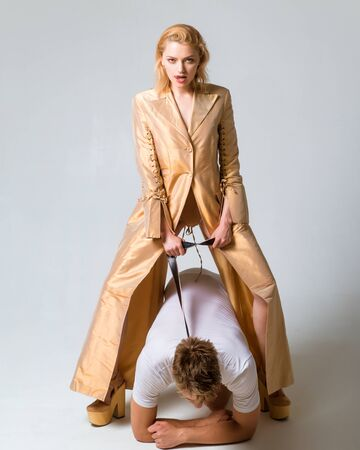 Young man and woman are engaged bdsm in sex. Concept of dominance. Woman holds man in lead. Madam controling her sexual slave. Powerful dominatrix woman concept.