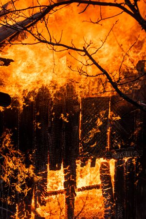 Fire everywhere and smoke in a residential area at night. Dangerous fire. Whole house and yard on fire. A fire destroys a charred burnt house. Charred in flame house at night. Stock fotó