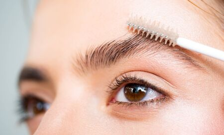 Eyebrows close up. Beautiful girl applies brow gel to her eyebrow. Close up portrait of young caucasian woman doing her eyebrow natural make up. Professional eyebrow make up concept.