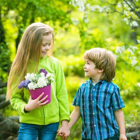 Vrolijk lachende jongen en meisje kijken elkaar aan en lopen naar buiten. Eerste liefde en kindertijd concept. Kleine jongen en meisje hand in hand. Kinderen vermaken zich in de lentetuin. Stockfoto