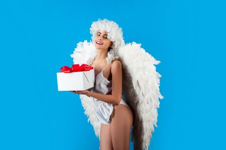 Angel woman with feather white wings and gift. Wonderful blonde angel girl with white wings. Art photo of a Angelic beautiful woman.