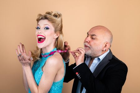 Happy blonde woman with luxury hairstyle and makeup smile while her sugar daddy wears a decoration on her neck. Rich elder man with grey hair. Blonde woman eye wink at camera. Stock Photo