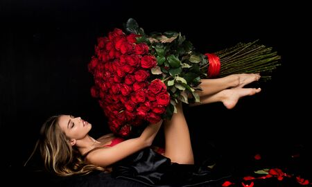 Beauty romantic woman with Red Rose flowers. Valentine. Fashion studio portrait of beautiful girl. Gift with love. Favorite flowers. Standard-Bild