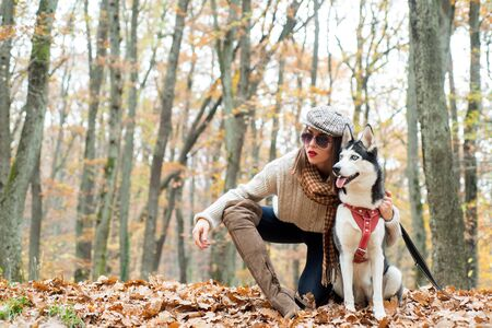 Pedigree dog concept. Wild in soul. Best friends. Girl enjoy walk with husky dog. Girl pretty stylish woman walking with husky dog autumn forest.