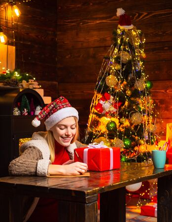 Woman is writing a christmas letter. New Year mood. Attractive woman in a Christmas room. Happy woman with Christmas gift over Christmas interior background.