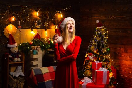 Young Santa woman holding glass of wedow champagne celebrates Christmas indoor at beautiful decorated room. Happy christmas. Indoor. Shopping sale. New Year. Gifts service.