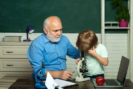 Friendly child boy with old mature teacher in classroom near blackboard desk. A grandfather and a toddler are learning in class. Educational process. Stok Fotoğraf