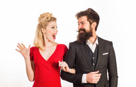 Funny retro couple. Blonde surprised woman in red dress looking at her bearded handsome future husband. Family photo of emotional young couple isolated at white background. Foto de archivo - 134790018