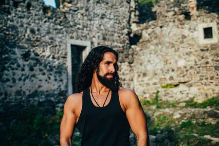 Strong healthy muscular man with long wavy hair and beard at ancient wall background. Mens style and wellness concept. Strong muscular handsome man walking outside.